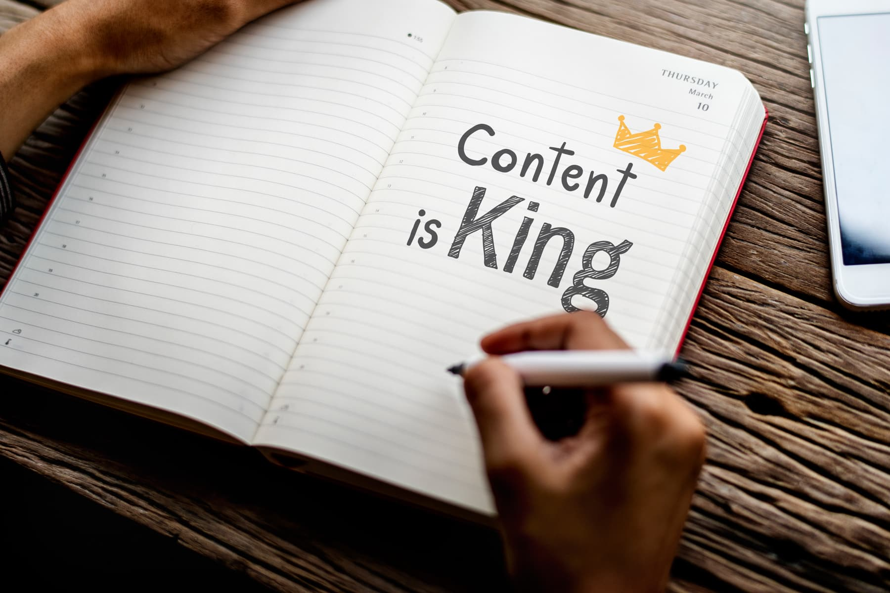 A close-up view of a person writing content is king in the opened notebook.