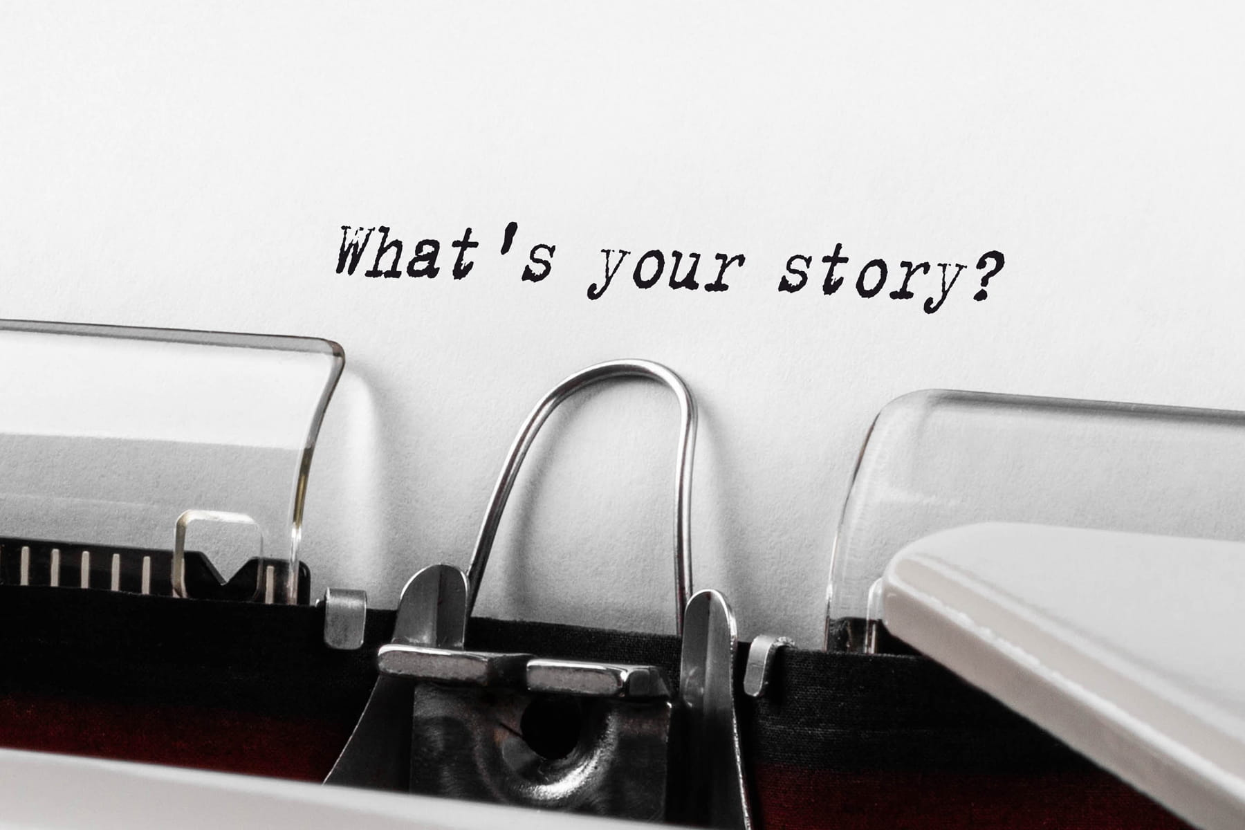 """A close-up of an old typewriter with words """"what's your story?"""" typed on a white paper."""