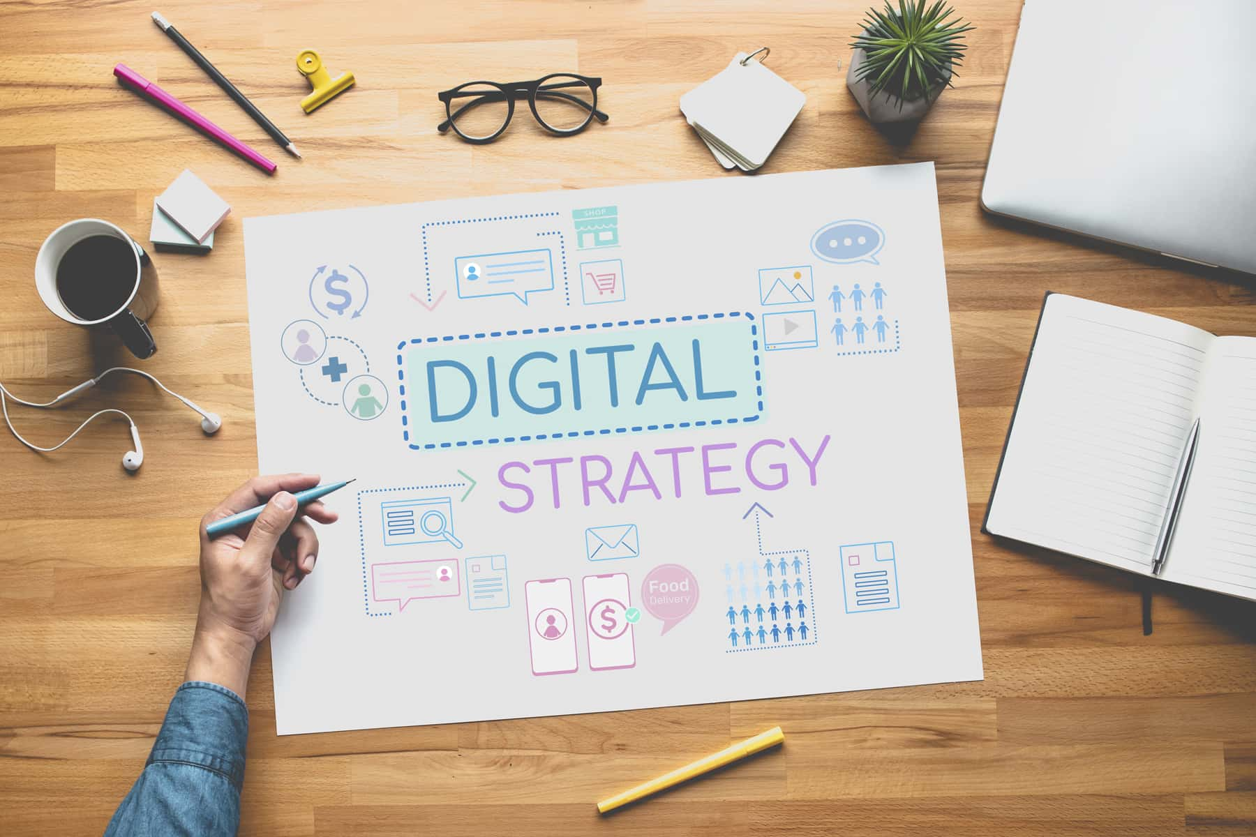 """A hand holding a pen and populating big paper with the words """"digital strategy"""" is finishing a marketing plan."""