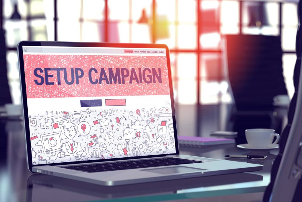 """A laptop screen shows the doodle design of a landing page with the big title """"Setup Campaign"""" optimized for a better conversion rate."""