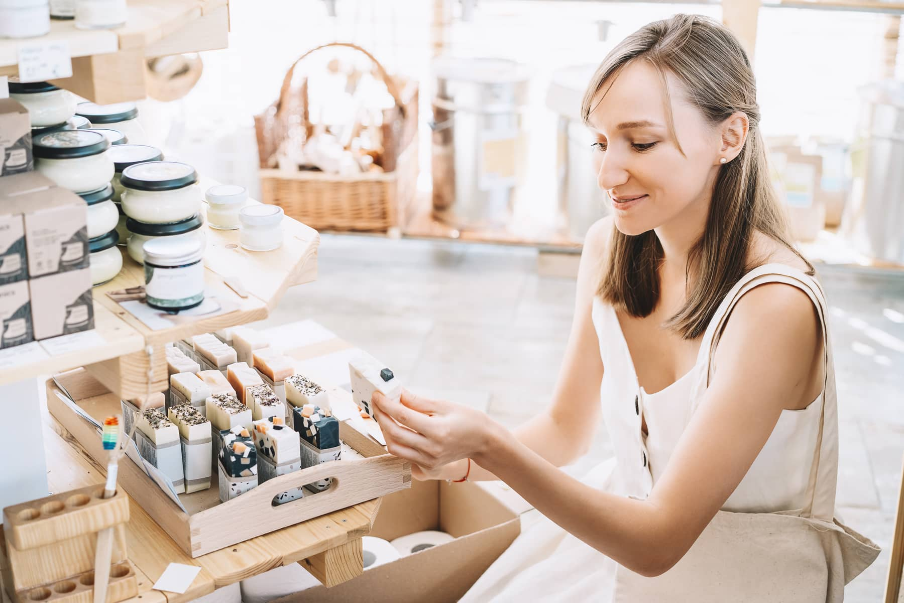 A young woman is browsing personal hygiene products in a small specialty store.