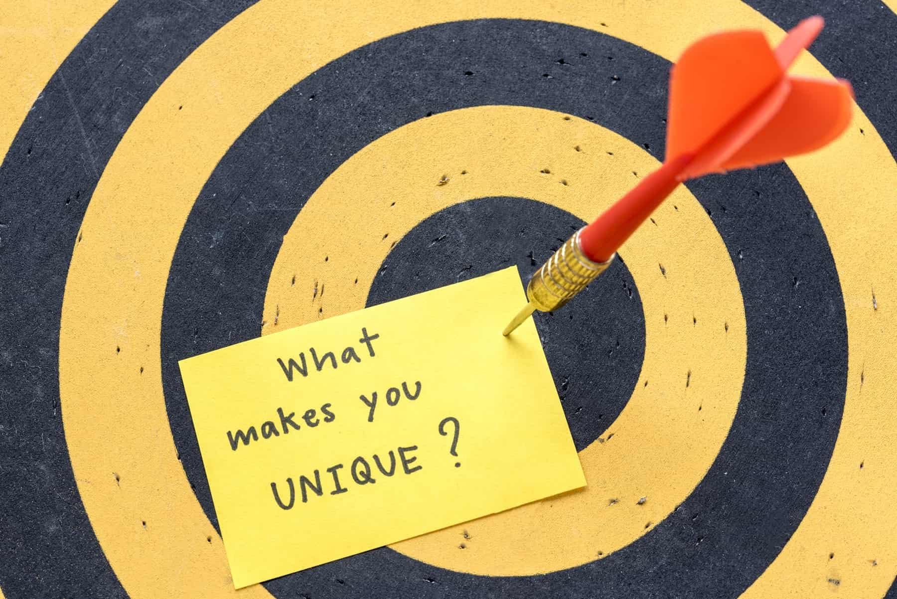 A close-up of a dartboard with a red dart stabbed in its centre holds a message on a piece of paper asking what makes you unique.