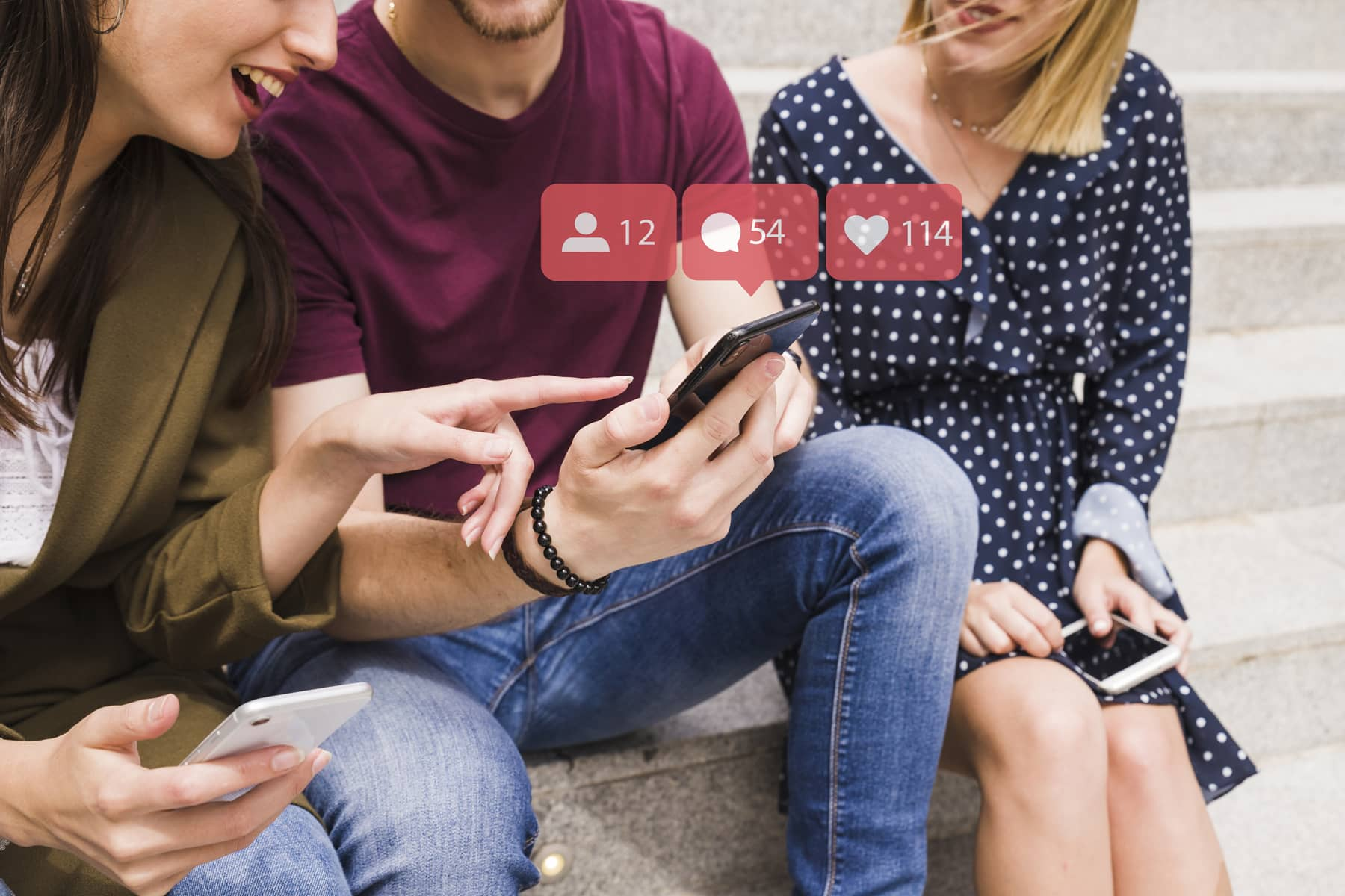 A close view of three young people laughing and discussing something they see in one's smartphone while social media marketing engagement icons fly across the image.