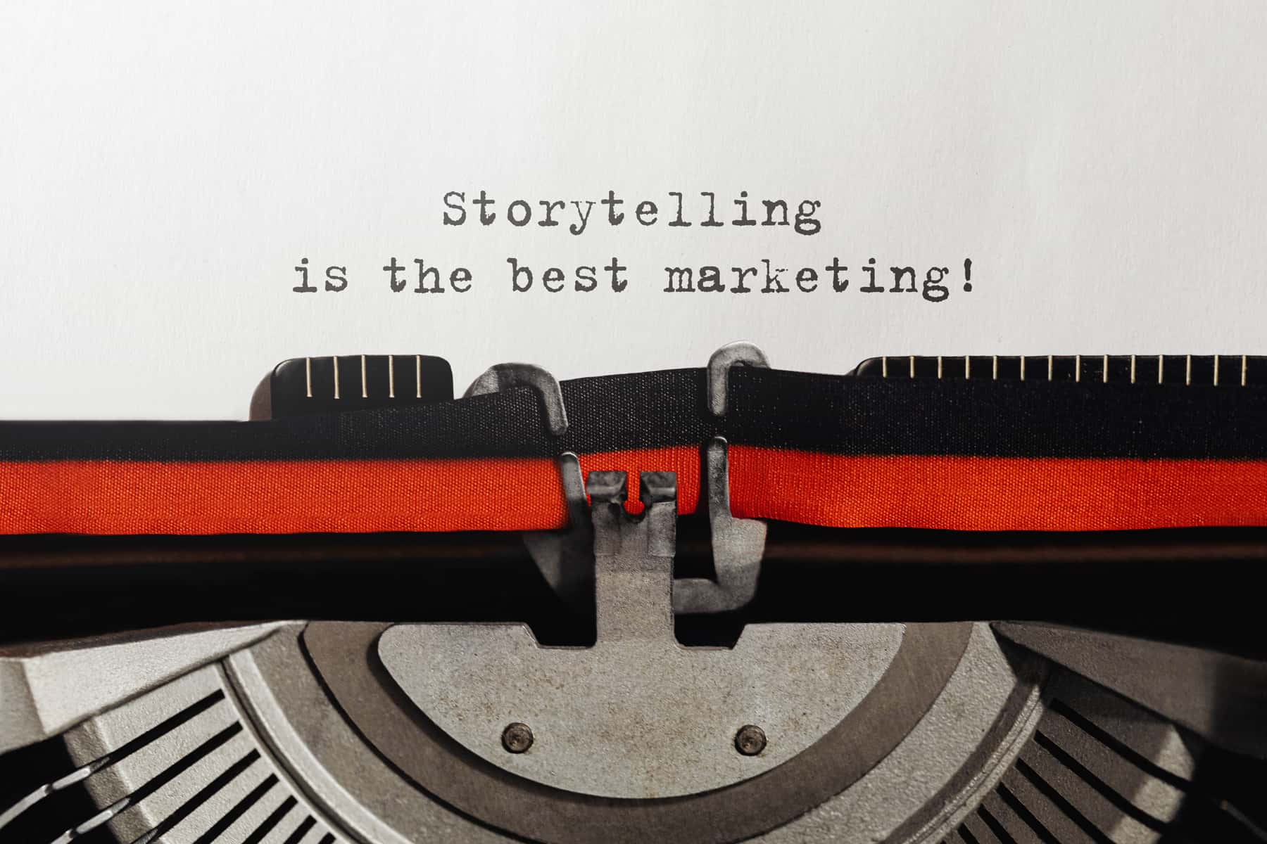 """Close view of an old-fashioned typewriter machine and words """"storytelling is the best marketing"""" typed on a piece of paper."""